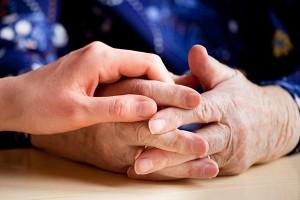 Main d'une femme plus jeune sur celles d'une femme âgée